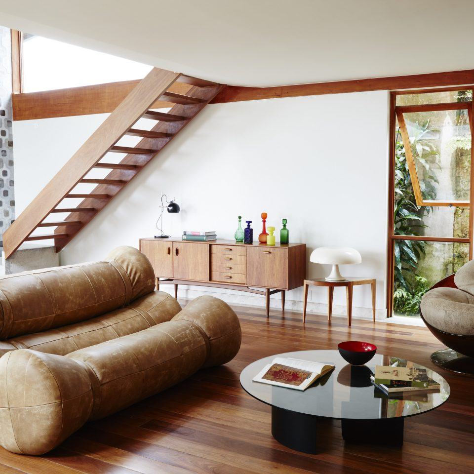 Spacious living room area with odd modern couch and round glass coffee table
