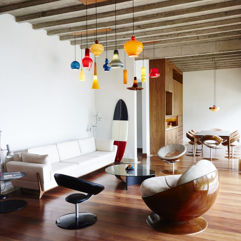 Living space with various hanging lights with a view of a dining table in the background