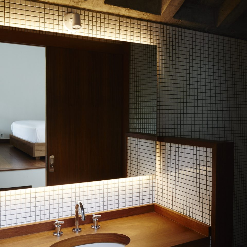 Bathroom with wall tiling and light seeping out from behind the mirror with a sight view of the bedroom in the reflection