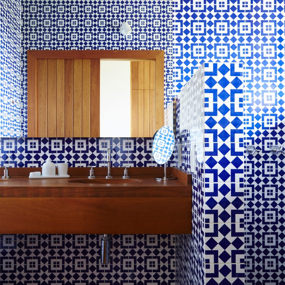 Beautiful white and royal blue tiled bathroom with wooden counter