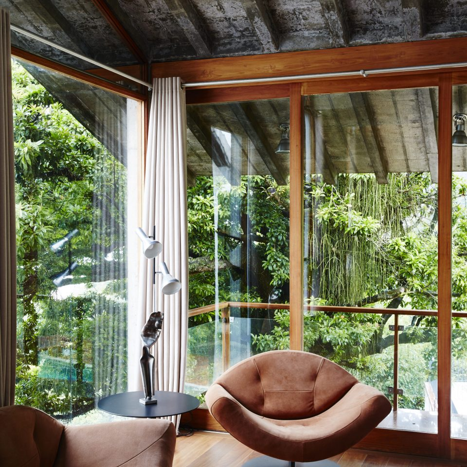 Seating area with open window view of lush greenery