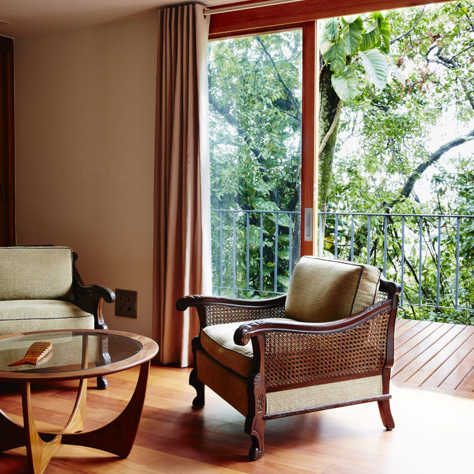 Seating area with doors open to balcony and views of lush greenery