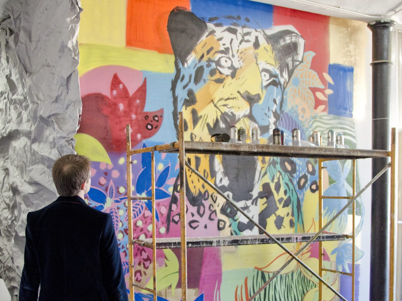 Man in a suit looking at a colorful wall art installation featuring a psychedelic leopard