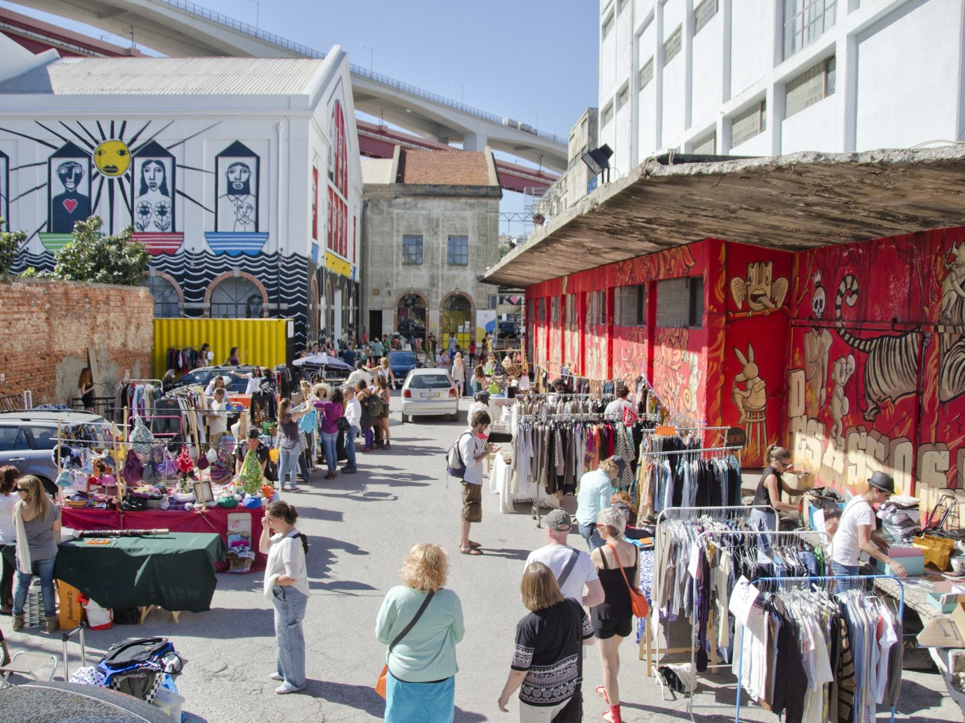 Outdoor market at LX Factory featuring tons of impressive wall art on building exteriors along with people shopping for hip second hand clothing