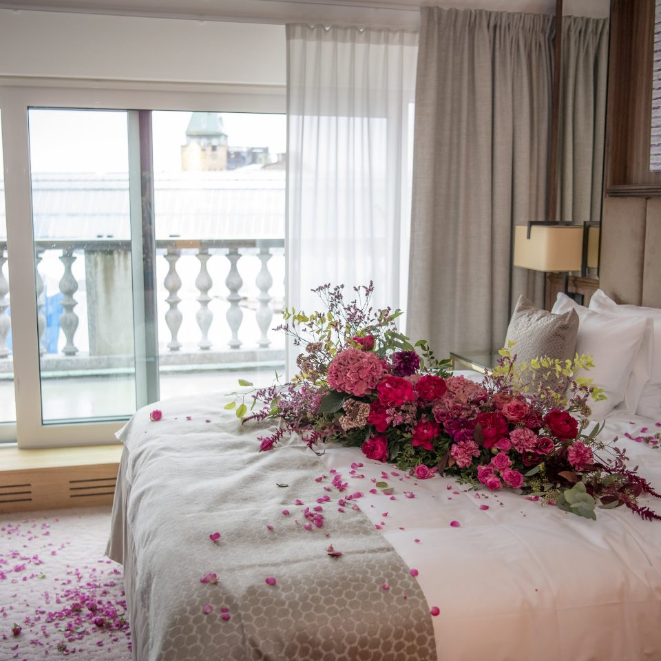 Bed with bushel of pink flowers and petals on it