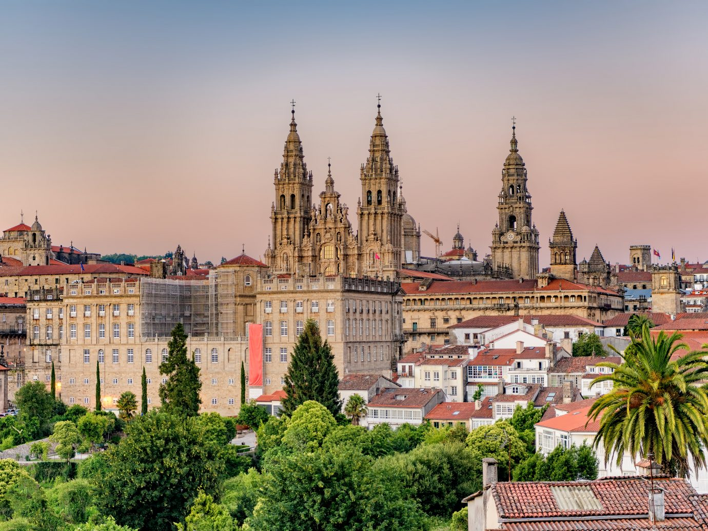 Hazy sunset on monumental Santiago de Compostela cathedral and cityscape.
