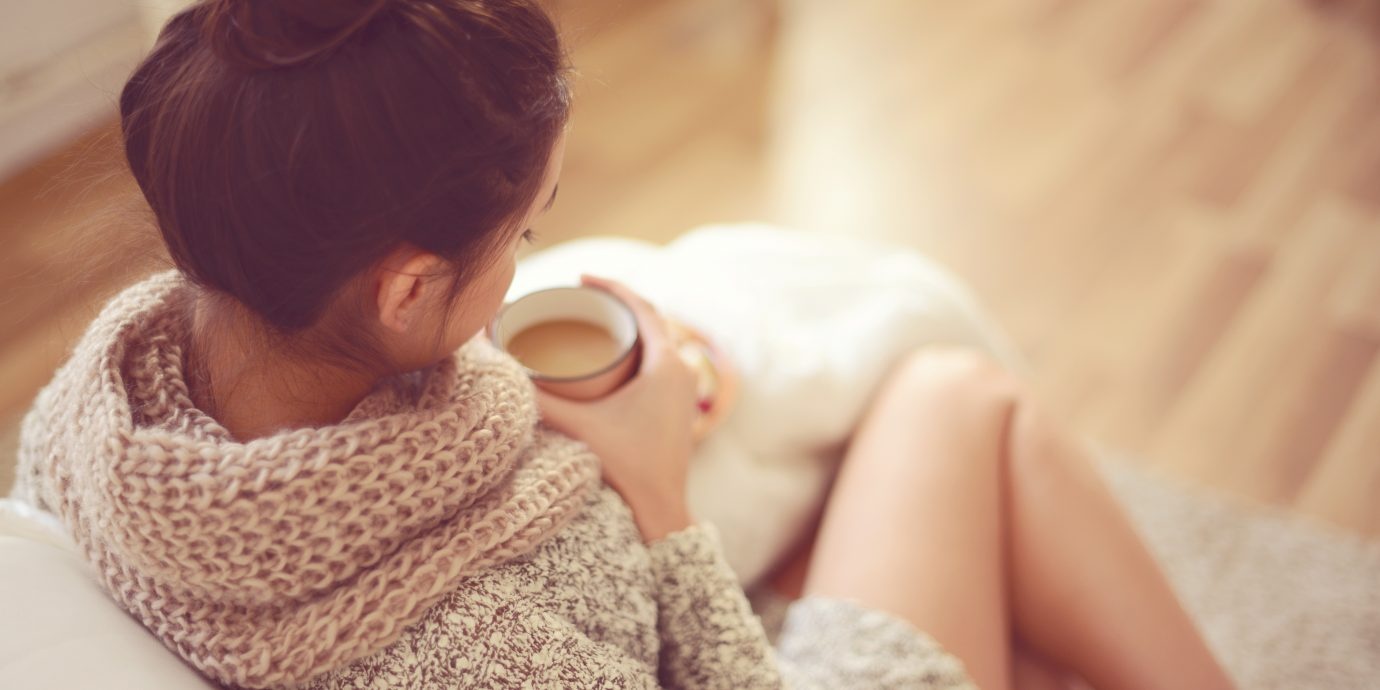 Everything you need for a cozy winter, young brunette woman in home interior.