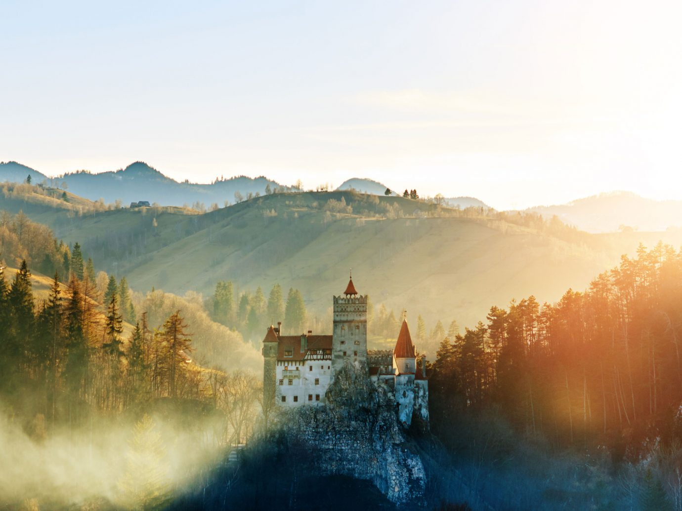 Bran Castle on a hilltop during a misty sunrise