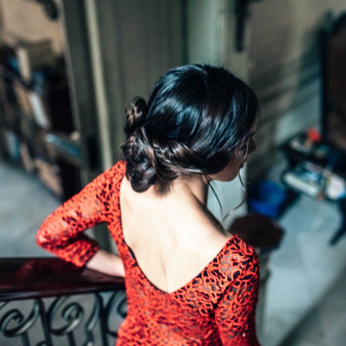 beautiful young cuban woman in red dress going down stairs in red dress