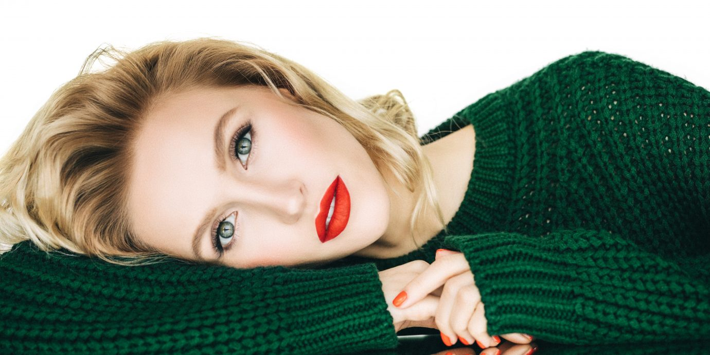 Beautiful woman wearing green sweater, Beauty Products for your winter routine