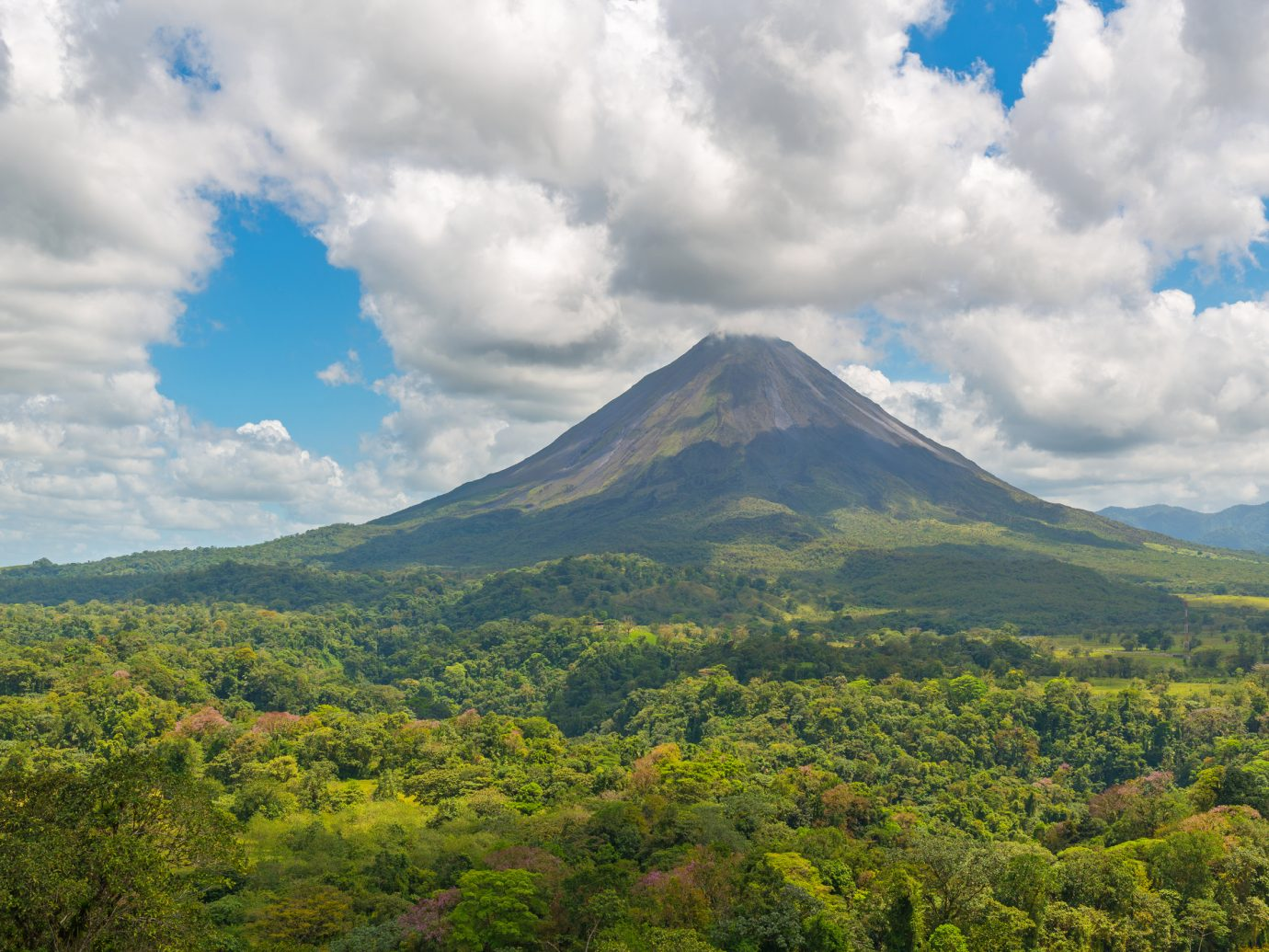 Landscape of the Arenal volcano surrounded by tropical rainforest on a sunny summer day near the cities of La Fortuna and San Jose, Costa Rica, Central America.