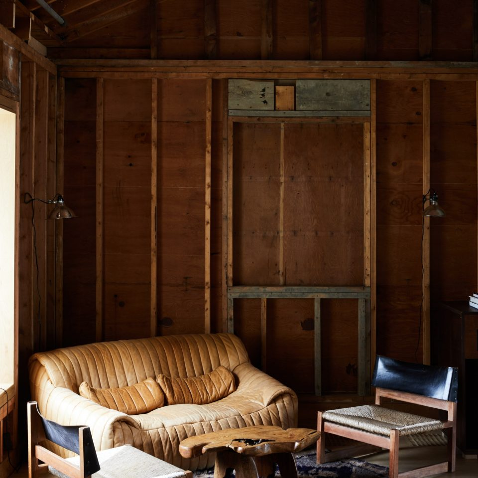Comfy brown couch and two chairs with a coffee table made from a tree trunk in corner of renovated barn room