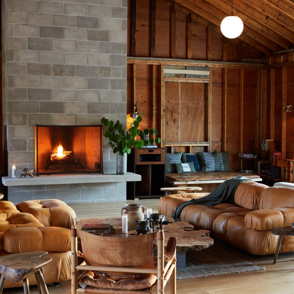 Another angle of the fireplace area with comfy couches, fireplace is lit