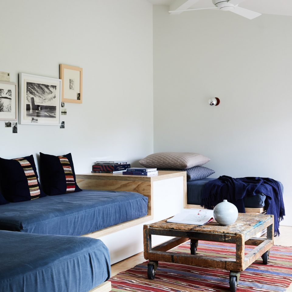 Navy makeshift couches on handmade wooden pedestal in a white room with a wooden coffee table on wheels