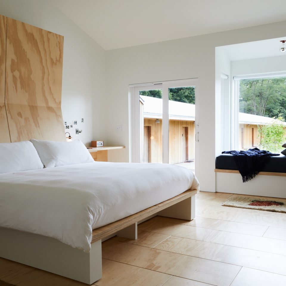 White bed in a white room on makeshift wooden pedestal with a wooden bed frame