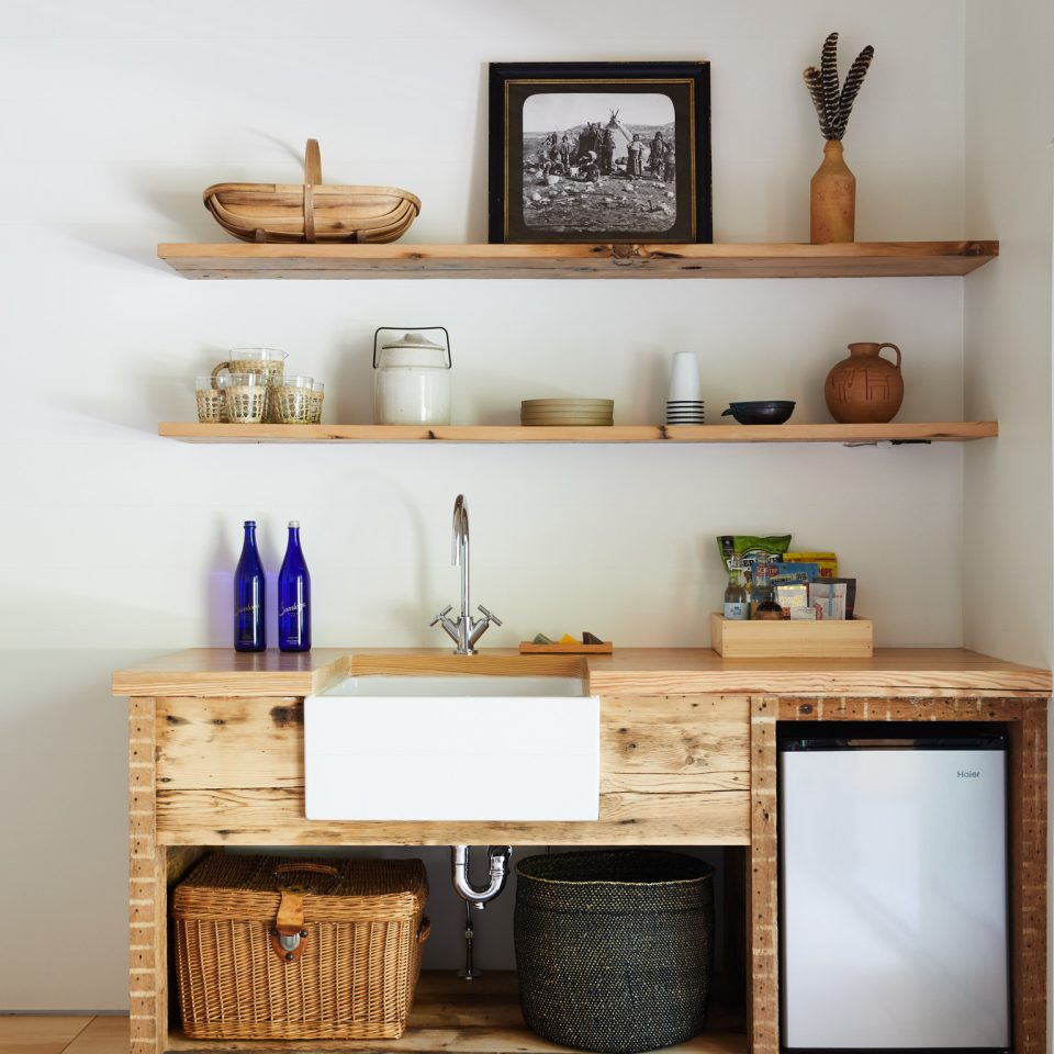 Sink and mini fridge in a makeshift wooden kitchenette