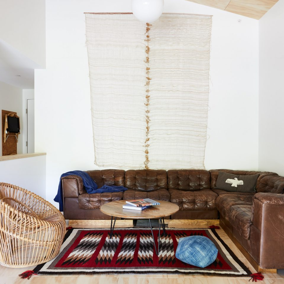 Dark brown wrap around leather couch in a corner of a white room with outdoorsy interior accents