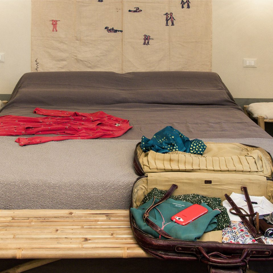 Open suitcase containing clothes, a camera, and a smartphone on a made bed with a red dress laid out at Casacau