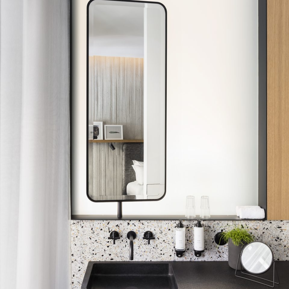 Modern looking bathroom with black rock sink and slim mirror at Hotel National des Arts et Métiers