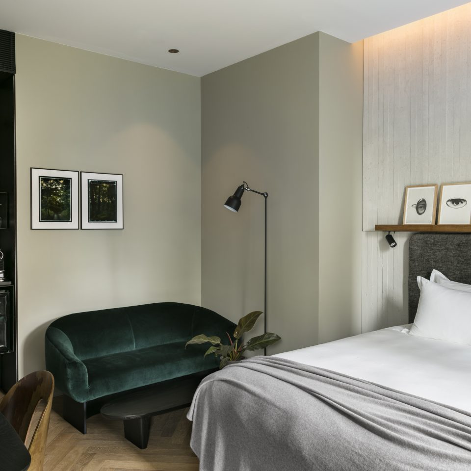 Interior of room with bed and green velvet couch at Hotel National des Arts et Métiers