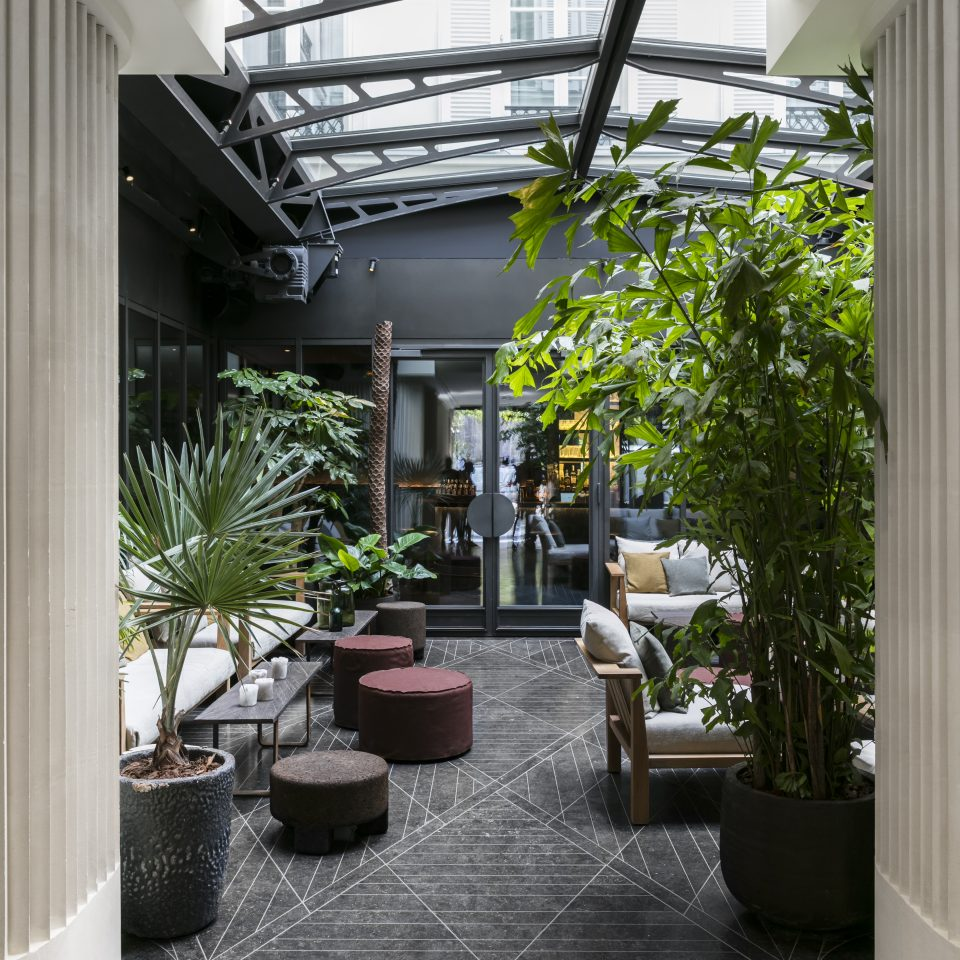 Lobby with house plants and seating with a roof window at Hotel National des Arts et Métiers