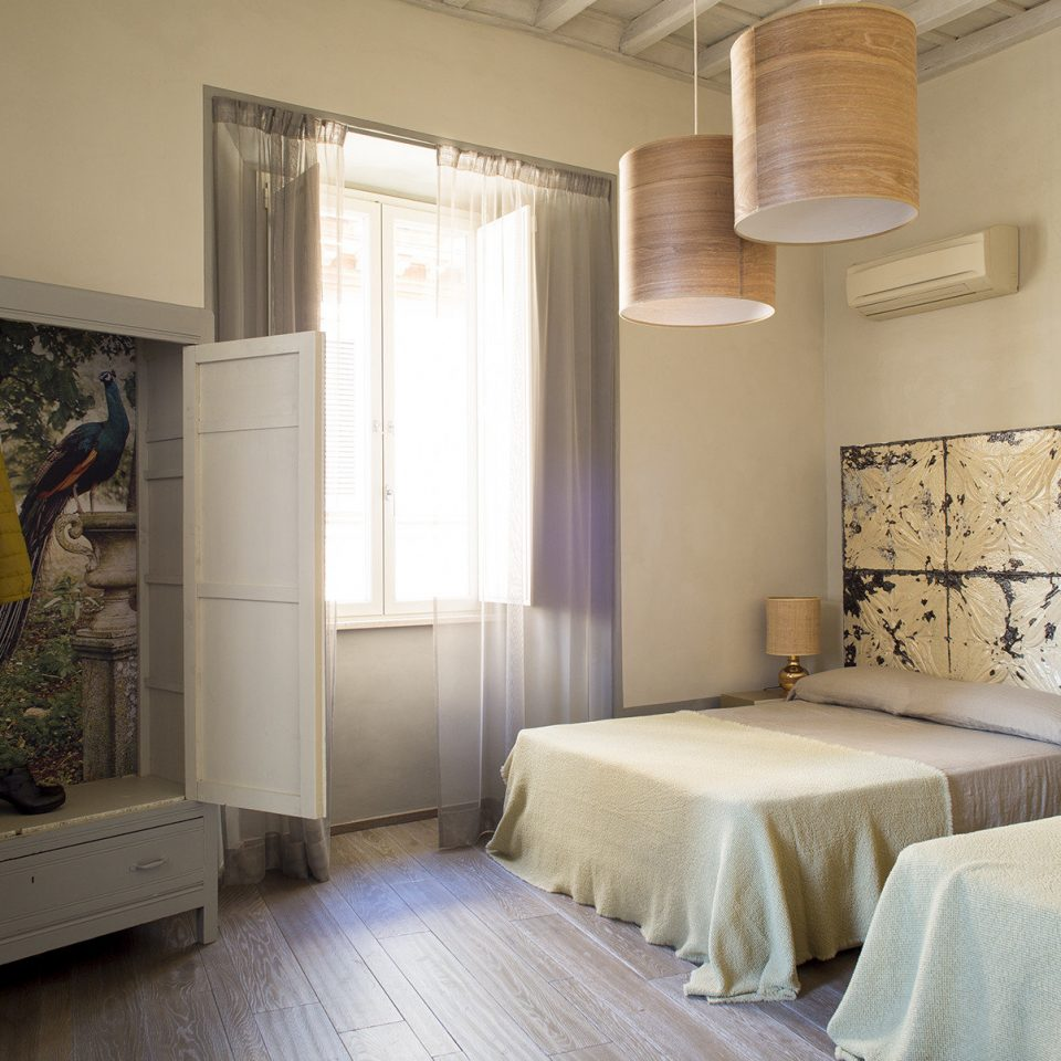 Double full bed room with open wardrobe containing a yellow jacket, a hat, and shoes at Casacau