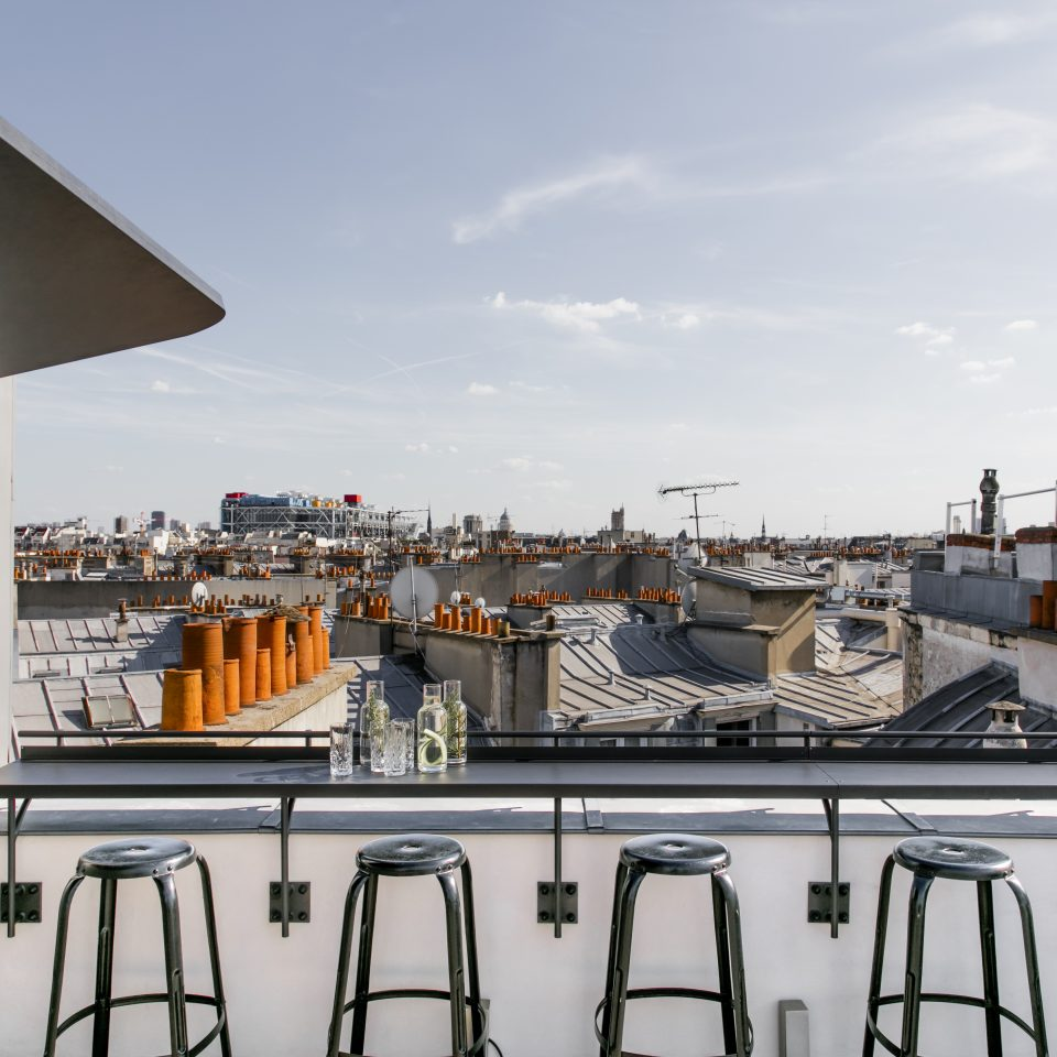 Rooftop with bar stools and ledge overlooking other rooftops in Paris at Hotel National des Arts et Métiers