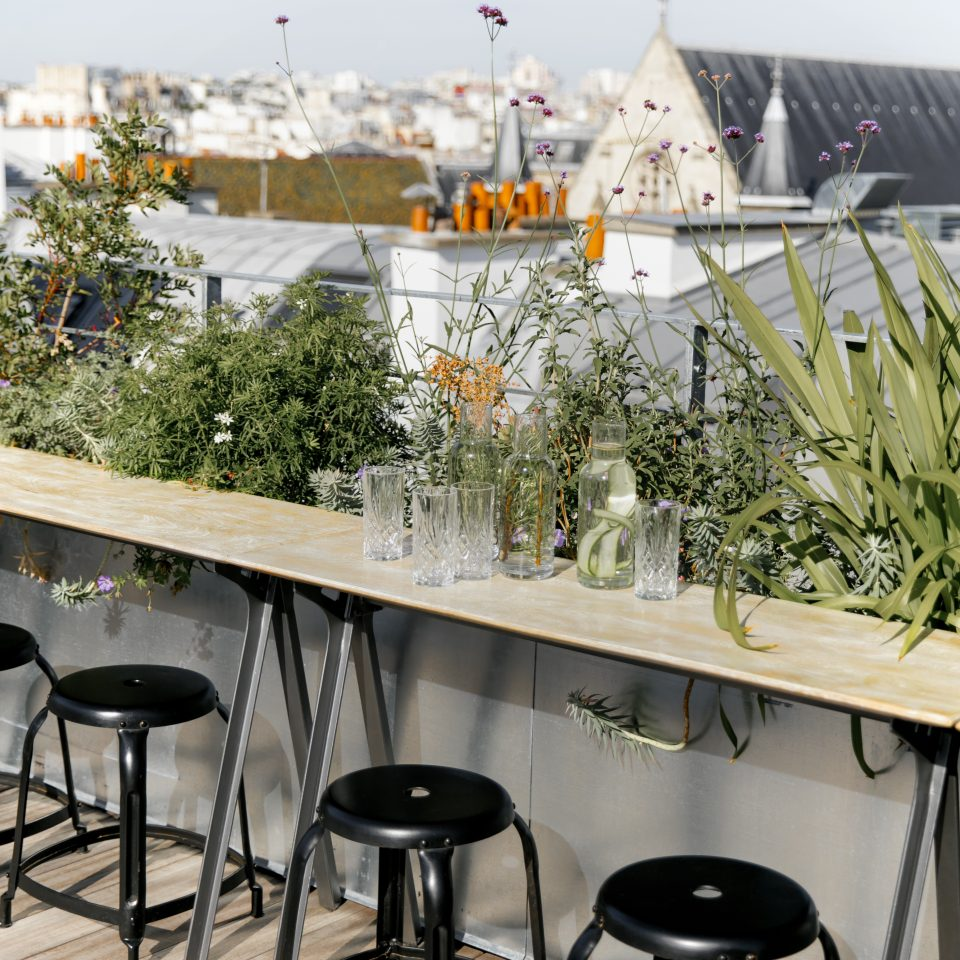 Ledge with barstools and plants on rooftop at Hotel National des Arts et Métiers