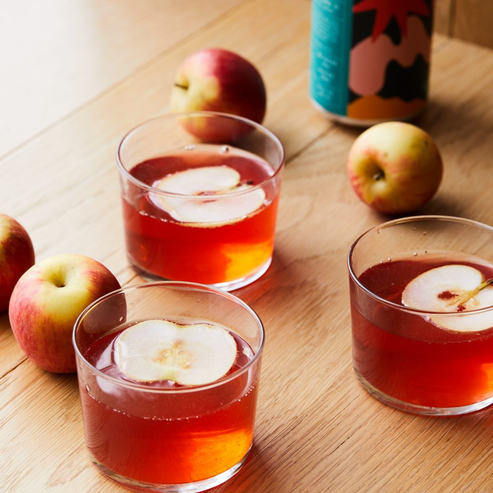 Apple cider cocktails with apples floating in them