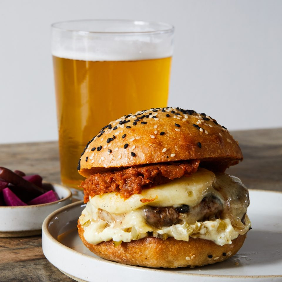 Burger with another orange meat and melty cheese dripping down the sides and a beer