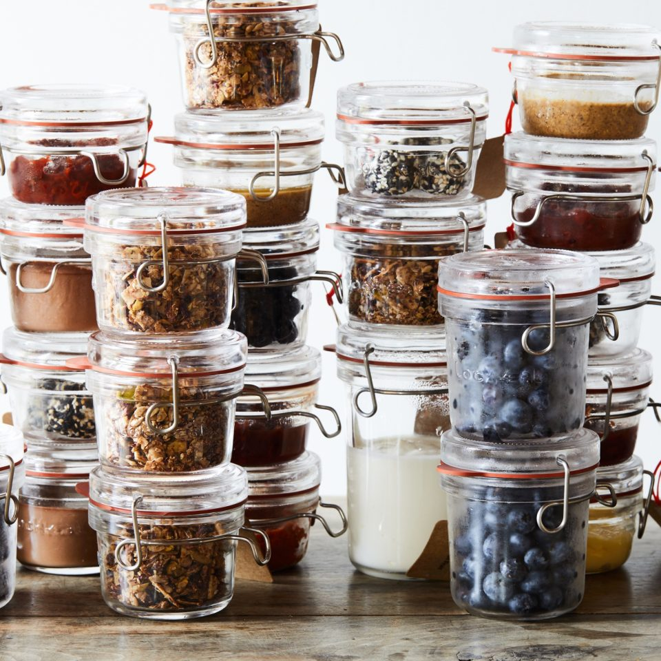 Stacks on stacks of clear mason jar-like containers with blueberries, jams, yogurts, nuts, and granola