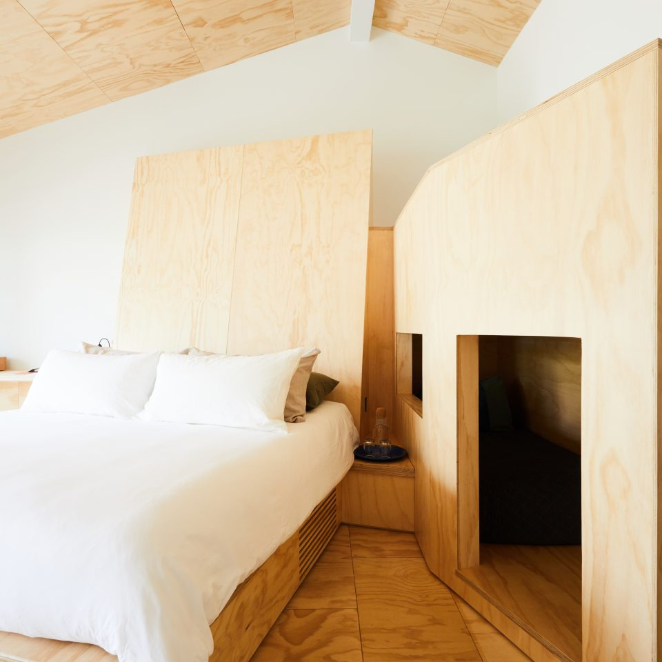 Room with a queen size bed and a bunk bed nook design for kids