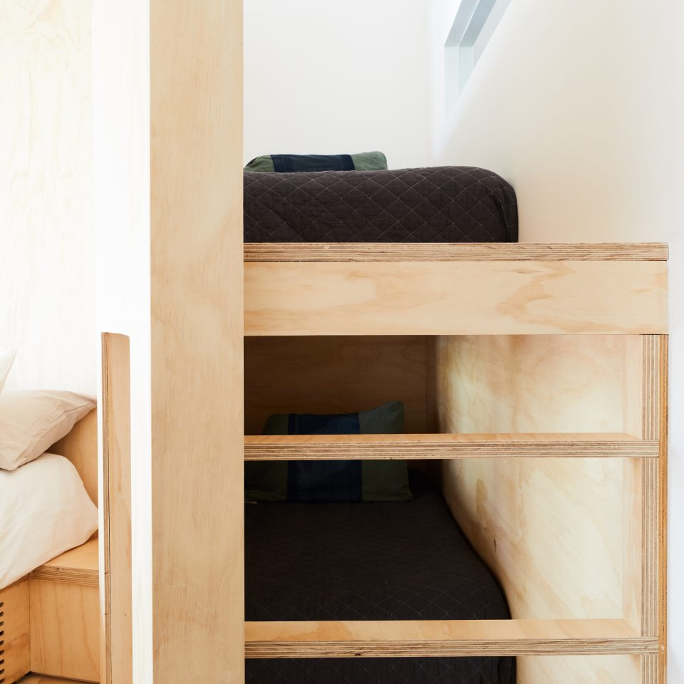 Closeup of bunk bed nook design featuring both top and bottom bunk including attached wide ladder
