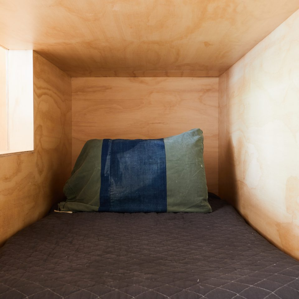 Interior of bunk bed nook design featuring a close up of one of the beds