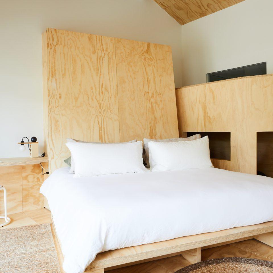 Queen size bed alongside bunk bed nook for kids