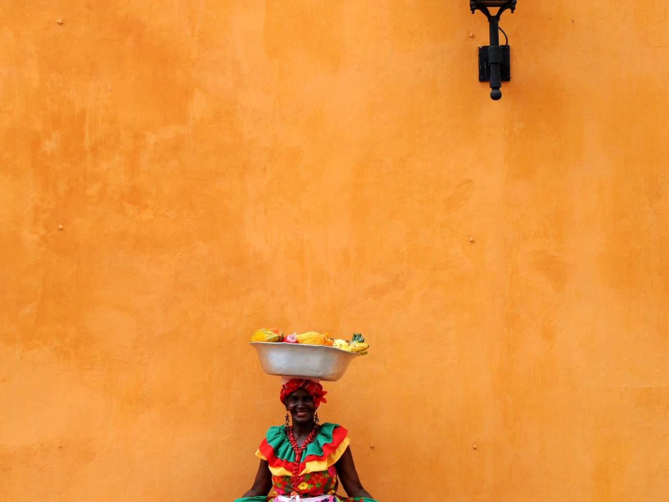 a local in Cartagena standing in front of a yellow wall in a beautiful colorful dress