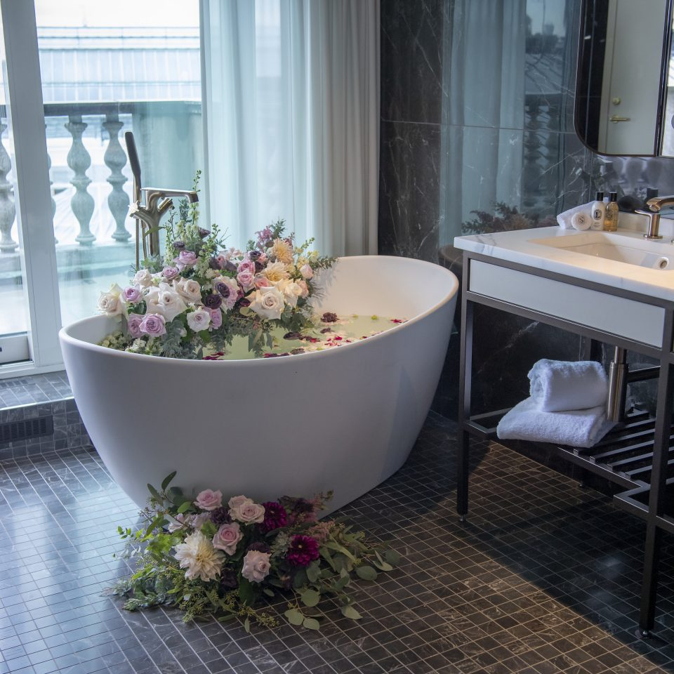 Beautiful bathtub with flowers floating