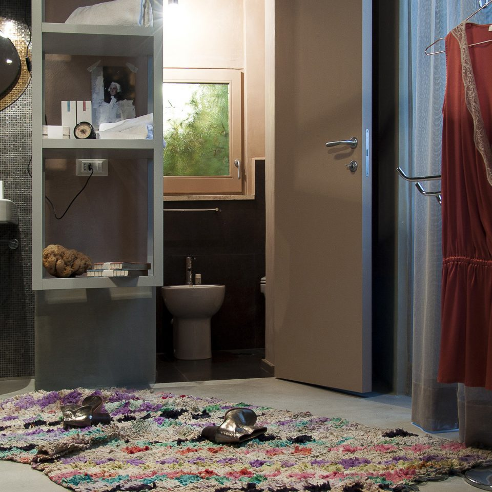 Messy bathroom scene with disheveled floor rug and a shoe on top at Casacau