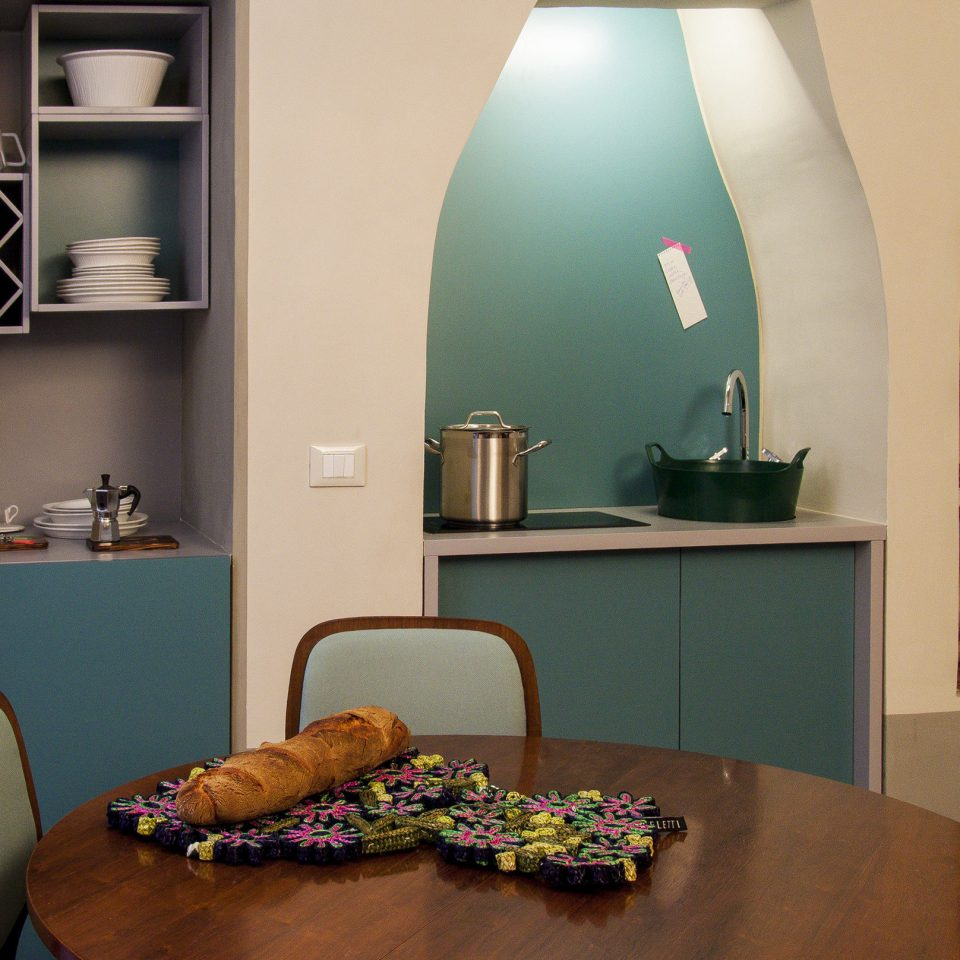 Kitchen with seafoam green accents and a wooden table with a loaf of fresh baked bread, Casacau