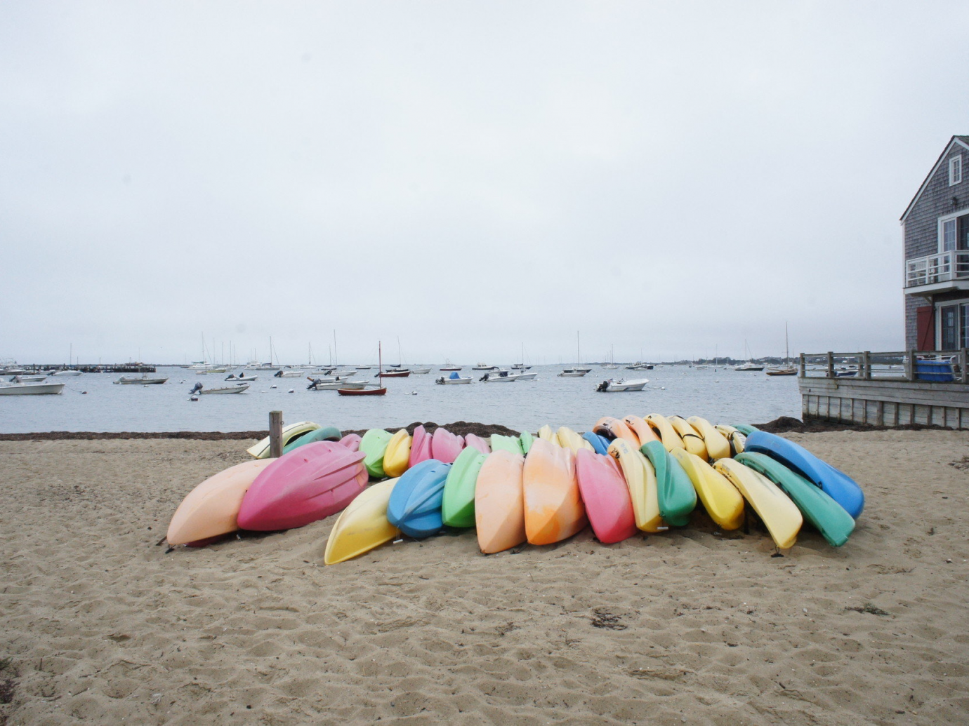 Canoes of assorted colors stacked on one another on a bay beach on a dreary day in Nantucket