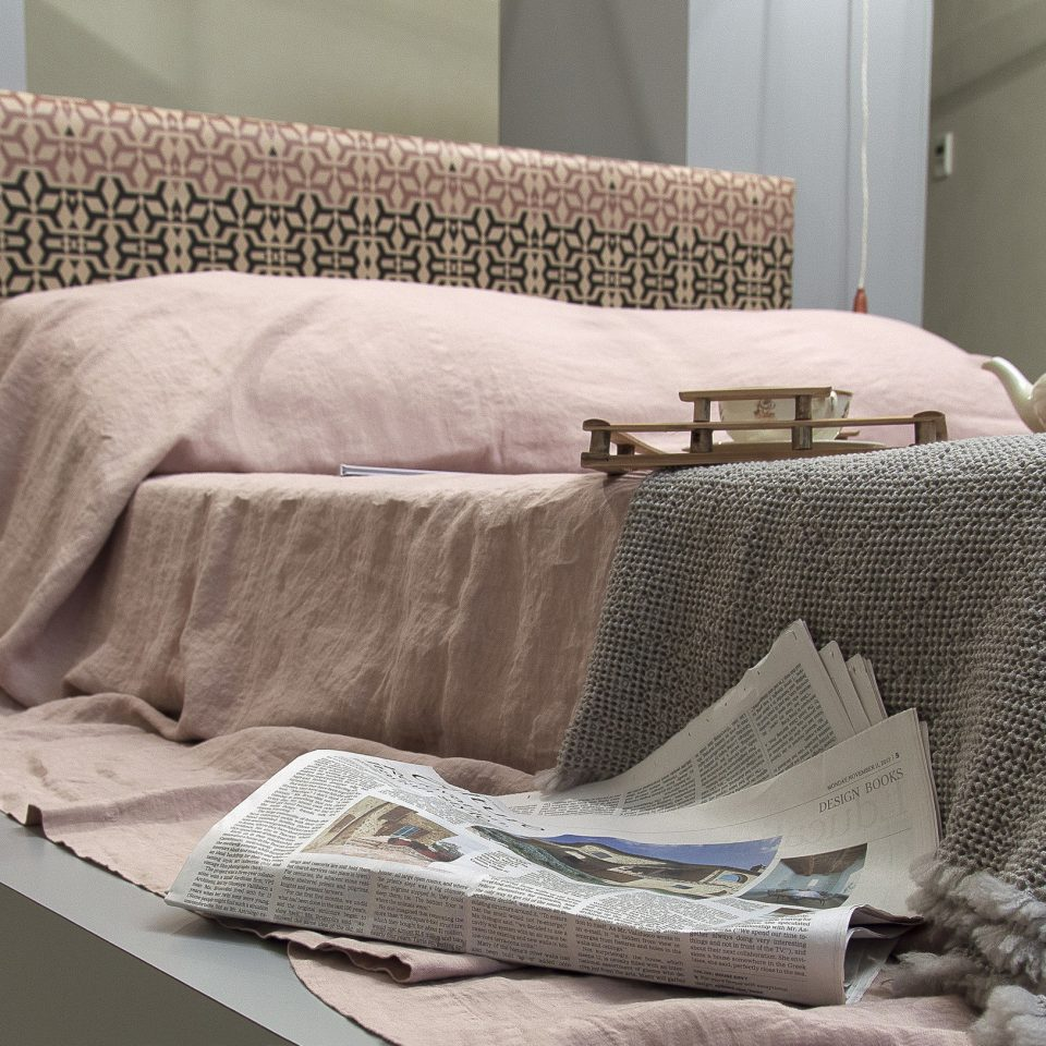 Messy pastel pink bed on pedestal with newspaper off the side, Casacau