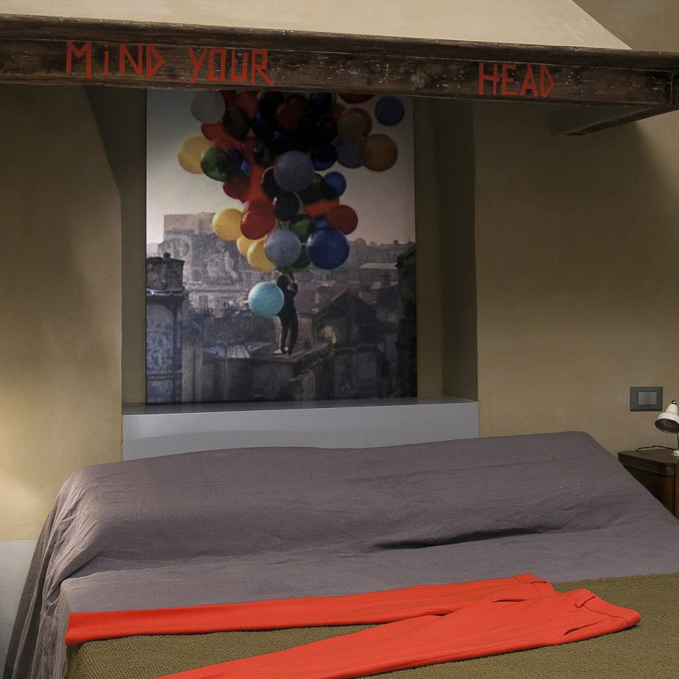 """Bed with red pants laid on top, shelf labeled """"Mind Your Head"""" above bed, Casacau in Rome"""