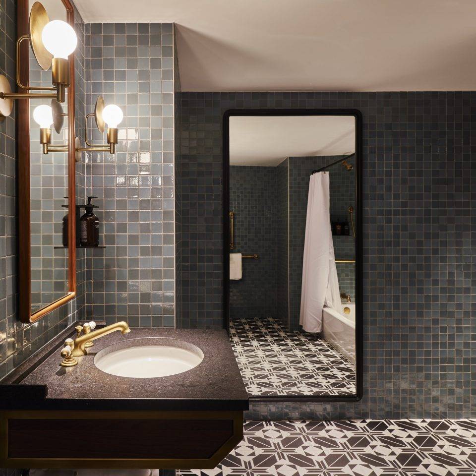 Large blueish grey tiled bathroom with full length mirror on the wall