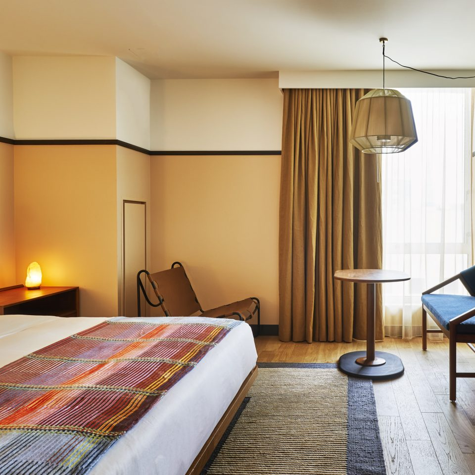 Hard wood floor room with salt rock lit lamp and white bed