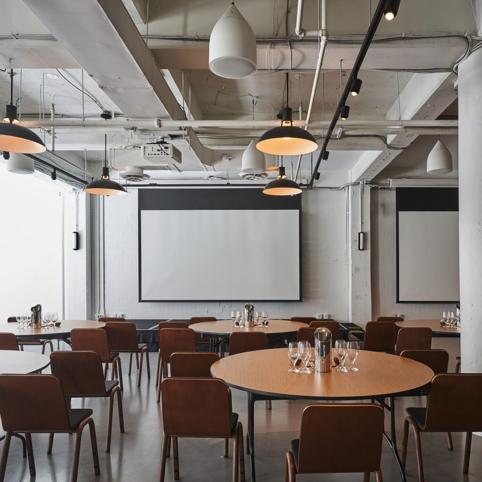 Restaurant at Eaton DC with circle tables and chairs facing two large projector screens