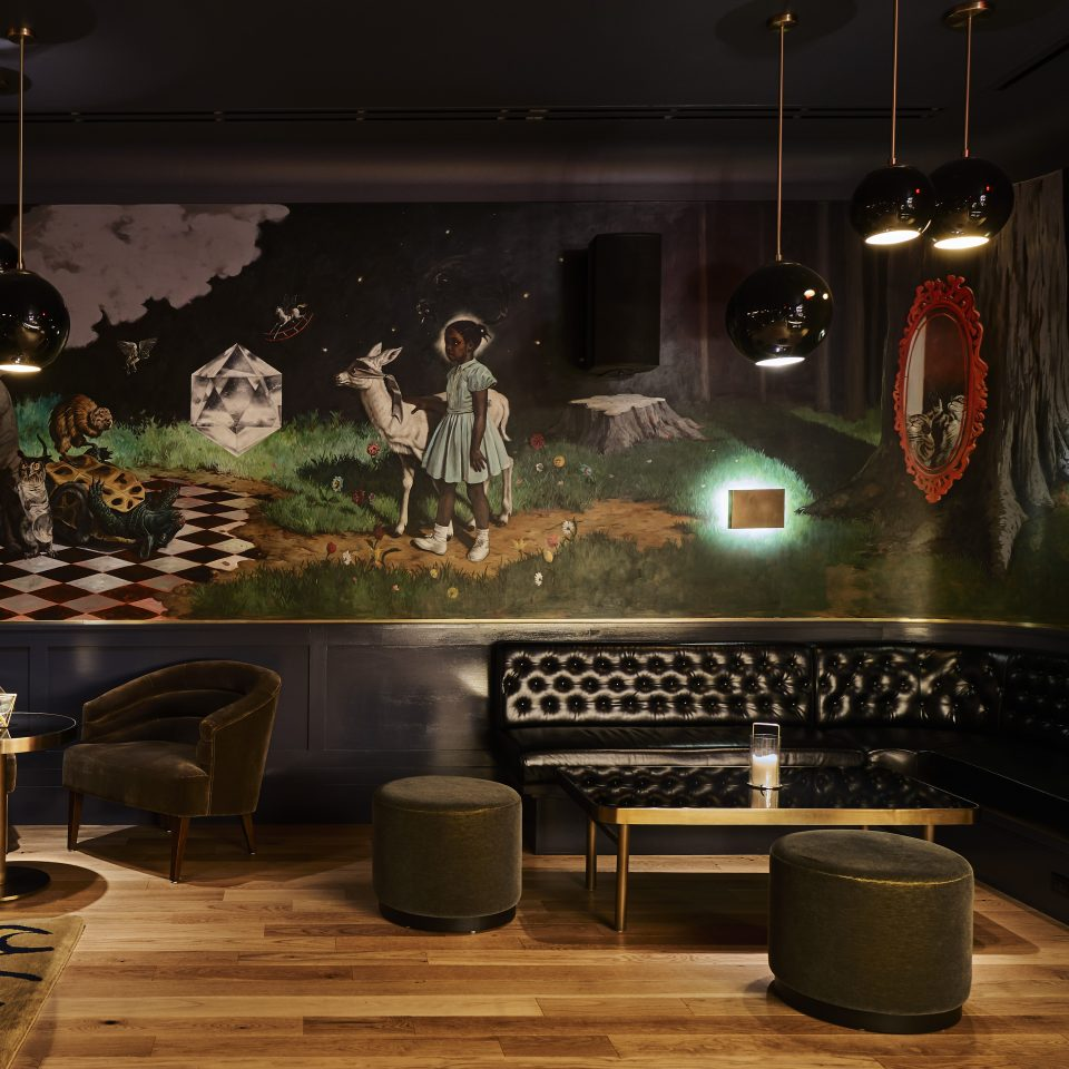 Sleek, dark room interior with a black leather couch and a gorgeous mural depicting a girl bringing a blindfolded lamb to other animals