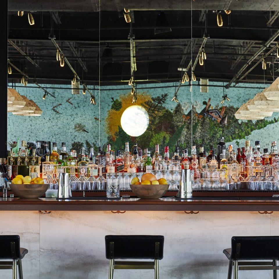 Set bar with mirrors on wall behind it, reflecting colorful wall mosaic