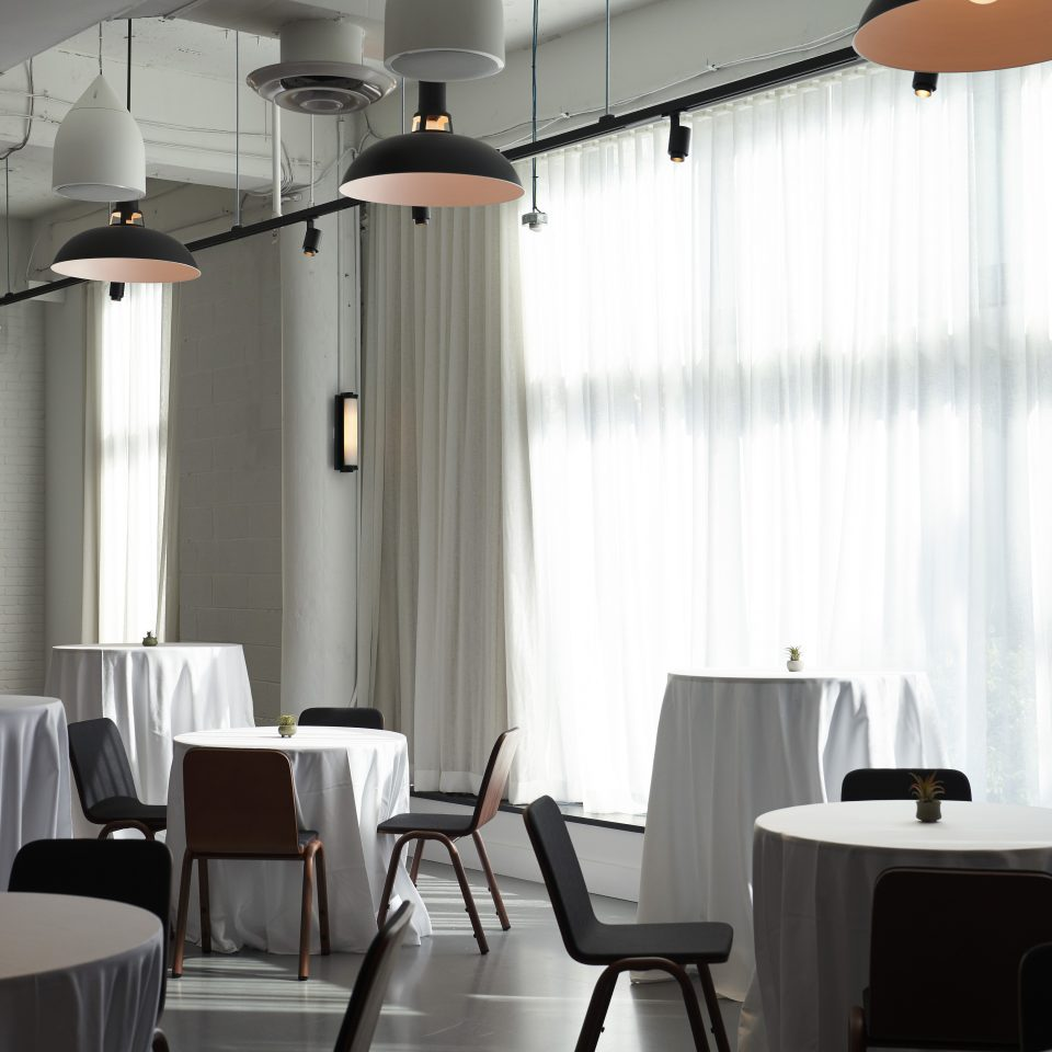 Room with circle tables draped in white table cloths as light pours in through sheer white curtains