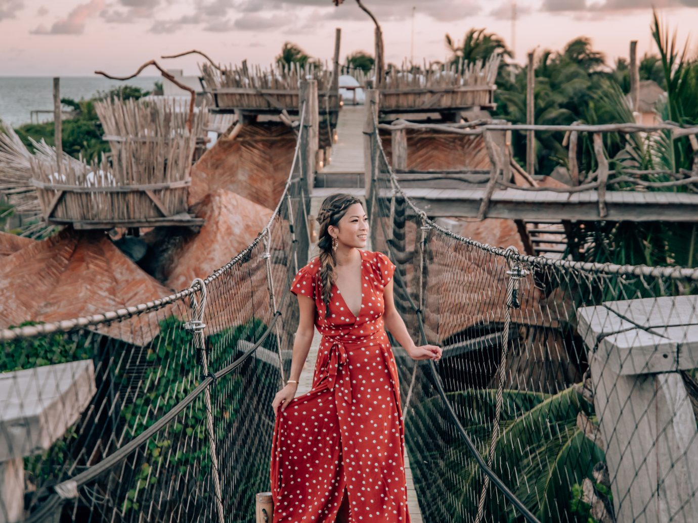 girl in a polka dot dress on a rope bridge