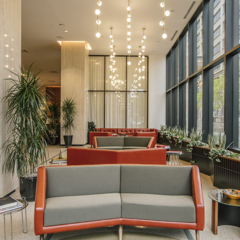 Modern lobby with red and grey couches, houseplants, and hanging ball on string light fixtures